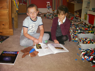 boy and girl reading with lego piles