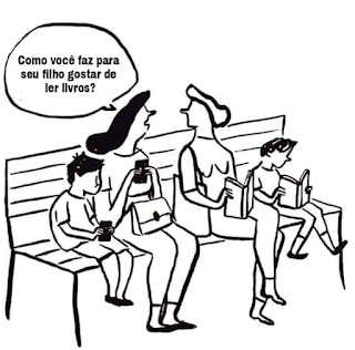 Desenho em fundo branco grafitado em preto. Quatro pessoas sentadas em um banco, ao centro, duas mulheres e ao lado de cada uma, meninos. À esquerda: mulher de cabelo escuro e comprido, segura um celular com as duas mãos, o filho também. À direita: mulher de cabelo claro e curto segura um livro entreaberto, o filho está atento ao livro dele. A mulher que está com o celular pergunta: Como você faz para seu filho gostar de ler livros? A mulher de cabelo claro apenas direciona a cabeça à que pergunta.