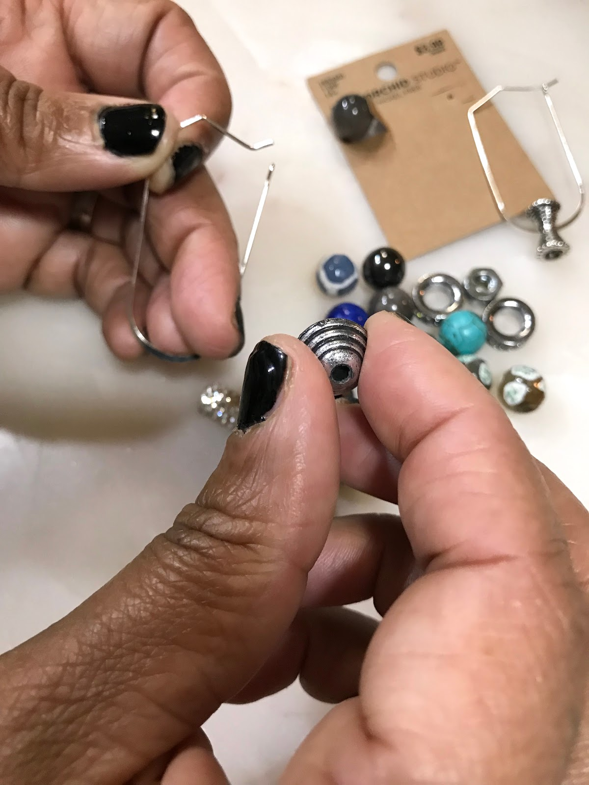 Imge: Diy Tips and hacks at home. Beads and charms being placed on earrings for a stylish look