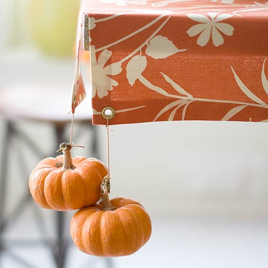 These hanging mini pumpkins from the tablecloth are cute for fall.