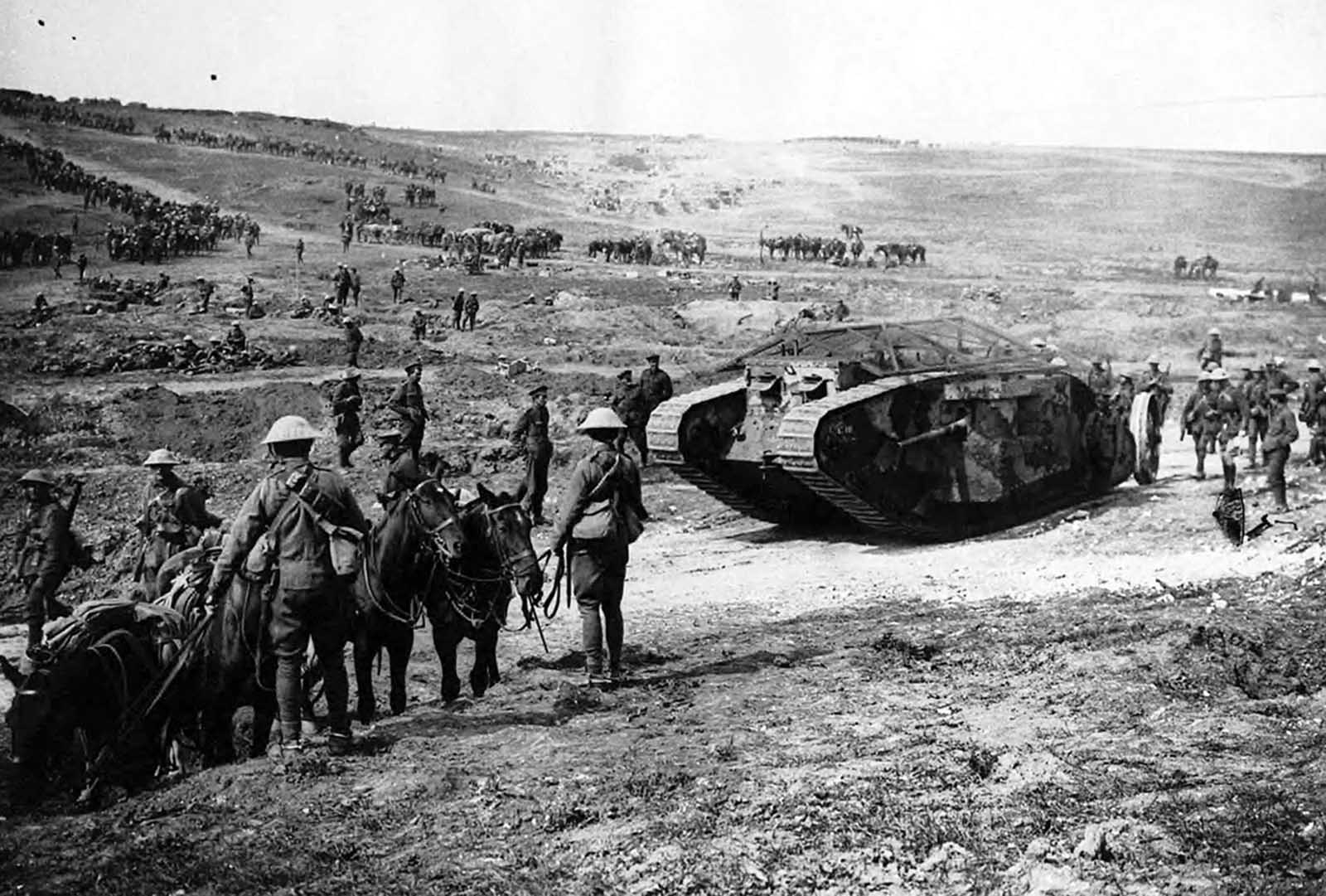 British Mark I tank, apparently painted in camouflage, flanked by infantry soldiers, mules and horses.