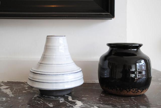 Twee keramieken vaasjes uit de shop van VT Wonen, een wit gestreepte van HK Living en een klein zwart potje van VT wonen op een marmeren mantel.