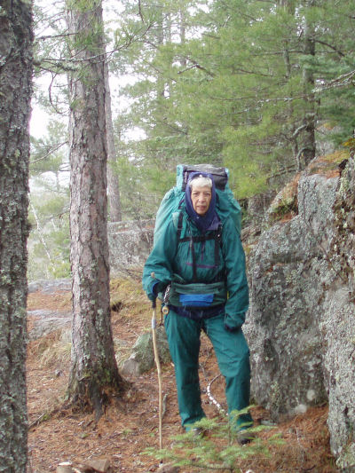 hiker on rocky trail in green nylon rain suit