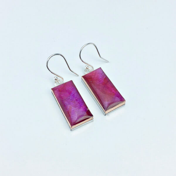 pair of painted pink and purple drop earrings with resin coating