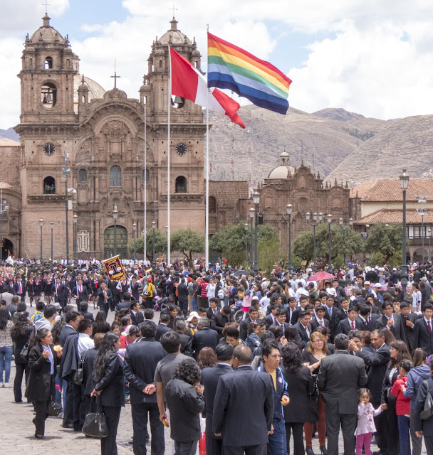 Cusco in 3 days: Plaza de Armas in Cusco Peru filled with a parade of students plus a rainbow flag