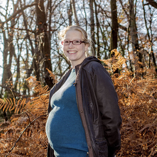 Standing in the autumnal forest with a 32 week bump