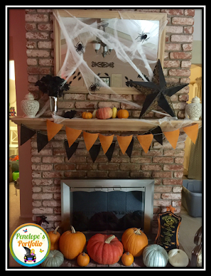 A fireplace and mantle decorated with pumpkins, spiderwebs, spiders, back flowers, and more