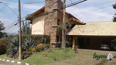 Vista da fachada da construção da casa, da entrada principal com a garagem com piso de pedra folheta com junta de grama e em volta a execução do paisagismo com pedras.