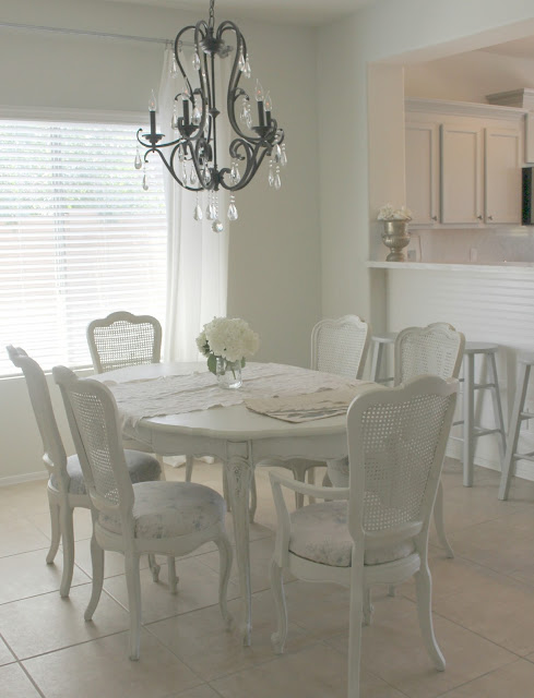 Shabby chic white dining room set with cane back chairs by Hello Lovely Studio