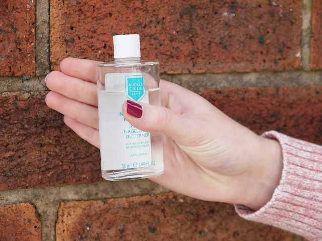hand holding the MicroCell remover against a red brick wall