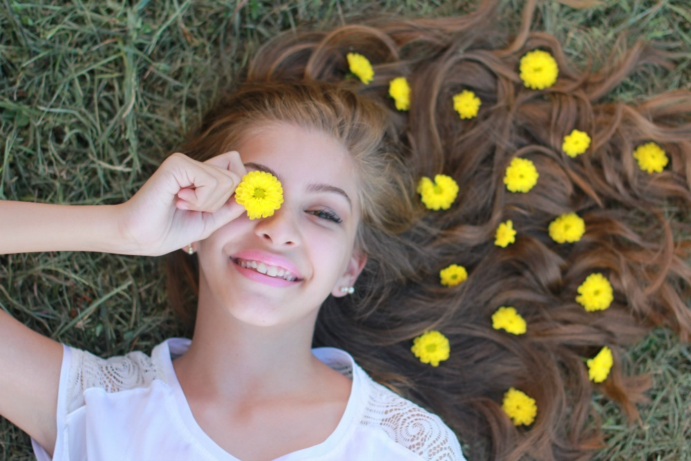 teen girl in the grass with flowers