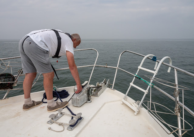 Photo of Phil bringing up the anchor in better conditions in the summer