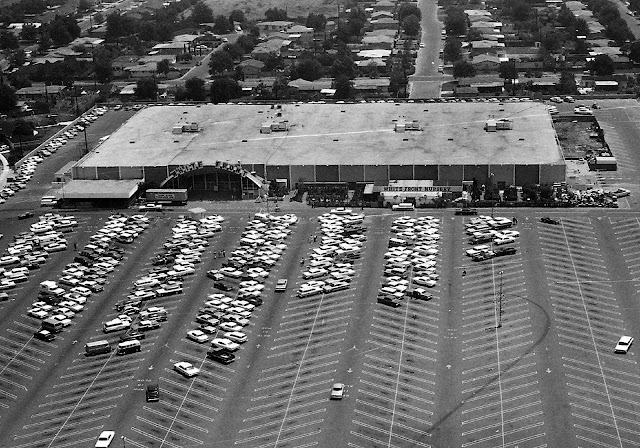 a 1960s shopping center parking lot, birdseye view photograph