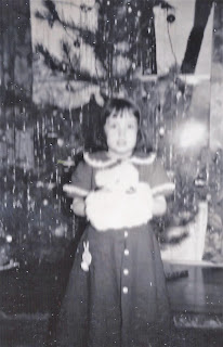 Photo of girl 8 years old, with Christmas tree, holding a fur muff.