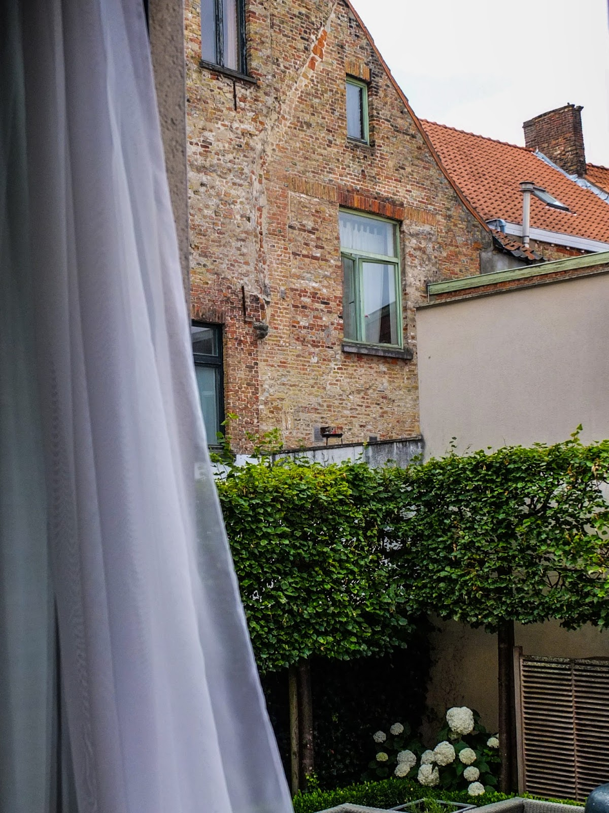 Window view overlooking a red brick wall of a house in Bruges with a curtain net in the foreground.