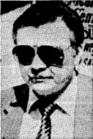 Headshot clipped from a newspaper, showing a round-faced middle-aged white man with short dark hair, wearing a jacket and tie and very large aviator-style sunglasses