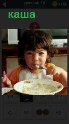 Ребенок за столом с ложкой ест из тарелки кашу