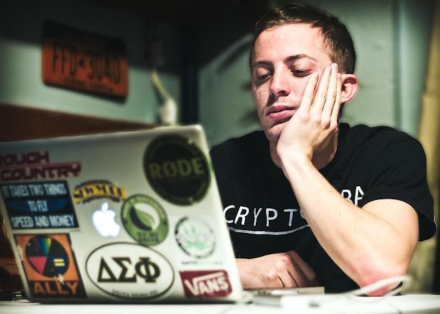 Hombre mirando la pantalla de su ordenador con cara de aburrido