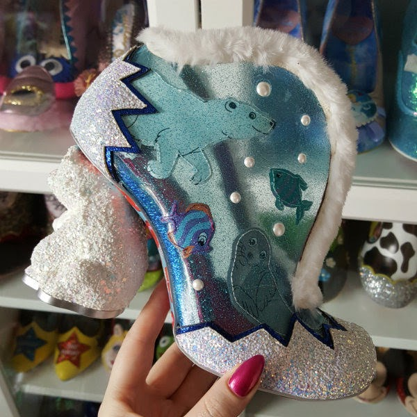 polar bear heeled and themed boot held in hand with shoe shelves in background
