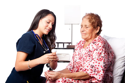 Nurse holding pill bottle while elderly patient looks at the bottle