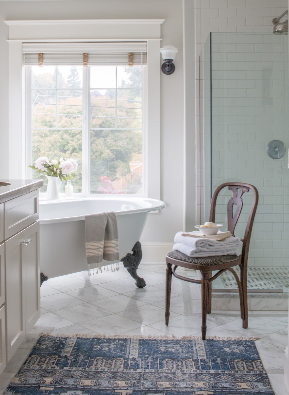 white clawfoot bathtub in bathroom with marble tile and white vanity and blue area rug