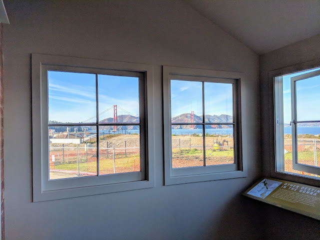 The Golden Gate Bridge is visible through windows at the back of the visitor center.