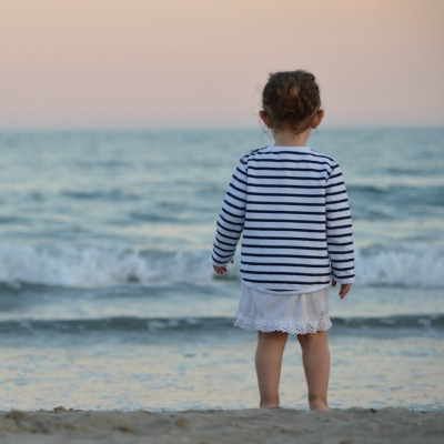 A photo of little girl standing at the water's edge on the beach, looking out to the horizon, taken from behind