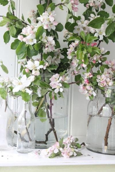 Botol kaca berwarna bening jadi vas untuk bunga putih