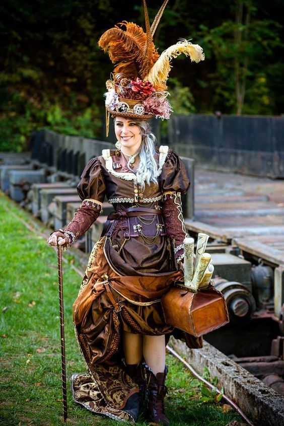 Woman in steampunk clothing in brown, orange, rust, red, copper) with feather hat, corset, skirt, cane