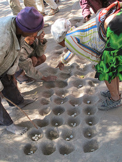 Mancala Oware is an ancient math skills African game. Mankala board dug into the ground photo by Leo Laempe