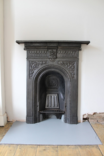 restored victorian fireplace with fireback and shelf