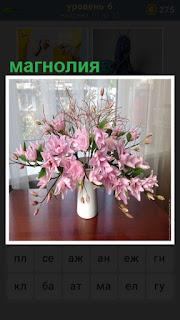 На столе стоит ваза, в которой находятся цветы магнолия