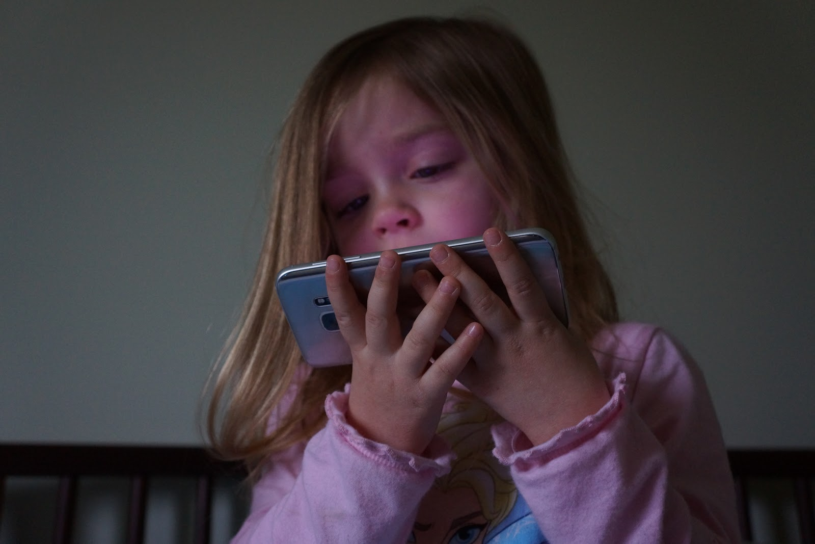 toddler girl watching a mobile film