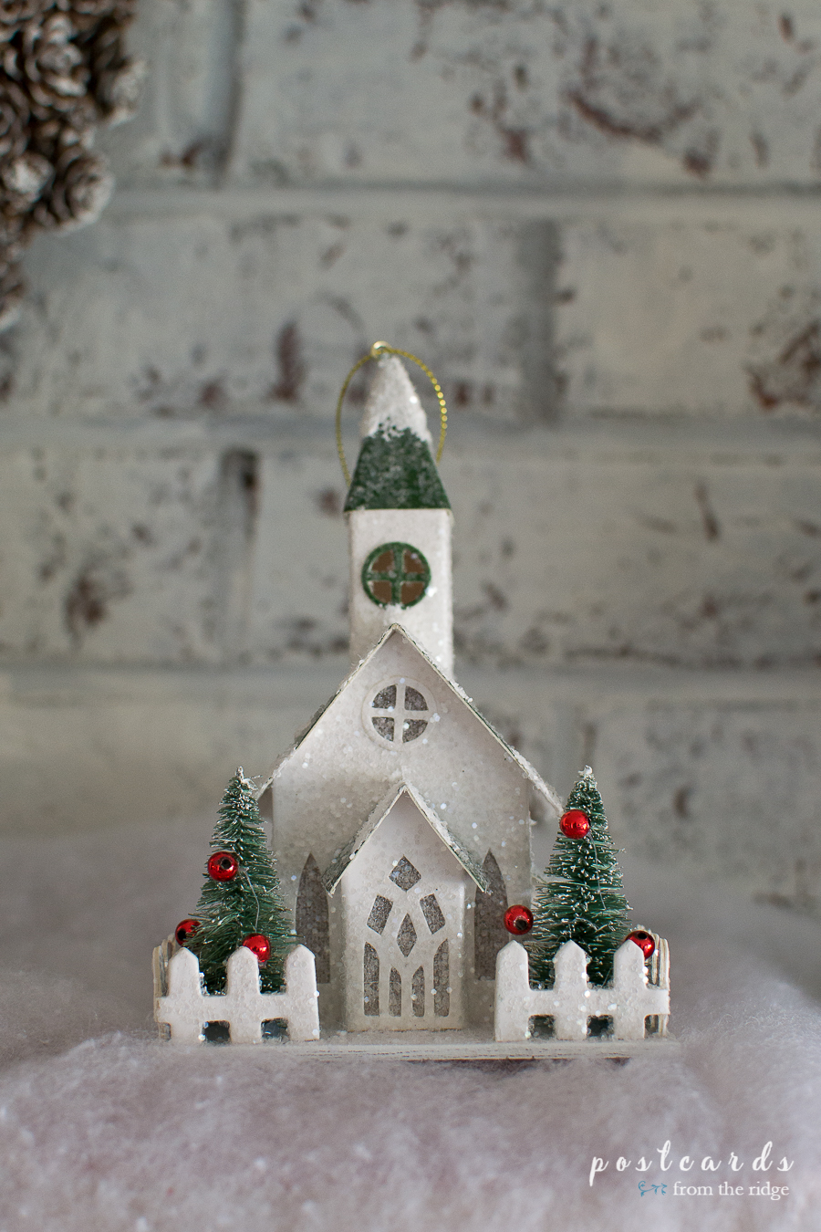 little snow covered paper church on a farmhouse Christmas mantel