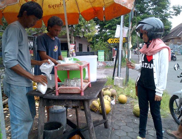 Penjual es kelapa muda saat melayani pembeli.