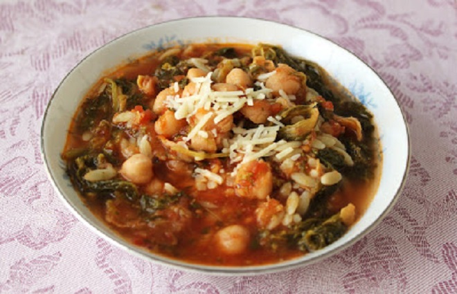 This is a bowl of pasta, garbanzo beans and broccoli rabe soup in a rich tomato broth