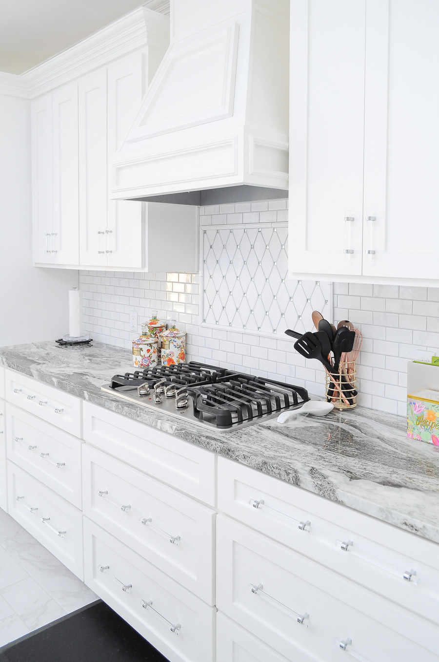 Bright white kitchen with fantasy brown granite, marble backsplash, thassos mirrored backsplash and lucite cabinet and drawer pulls.
