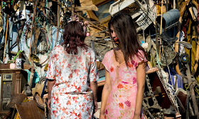 Zombie girl and her mother stand in front of a pile of junk