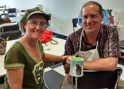 Cynthia M. Parkhill and Jonathan Donihue holding painted mug, angled so that painting of a black cat is facing outward toward viewer