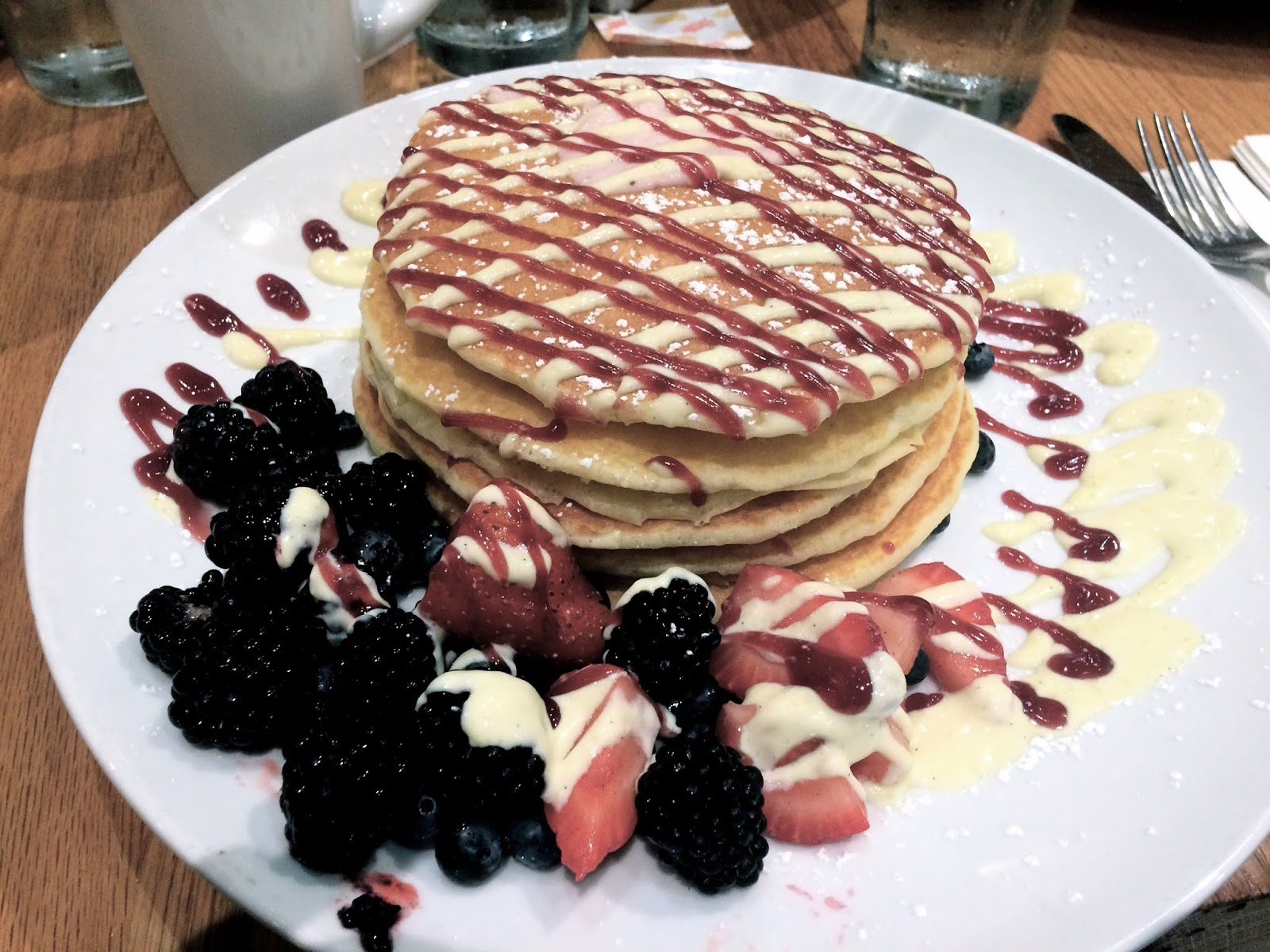 Pancakes covered in compote, strawberry cream and berries