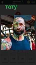 Мужчина покрыт с ног до головы татуировкой, в том числе на щеках лысой голове и на носу