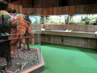 Room with full-scale models of Maori in traditional dress on the left, and a long diorama on the right.