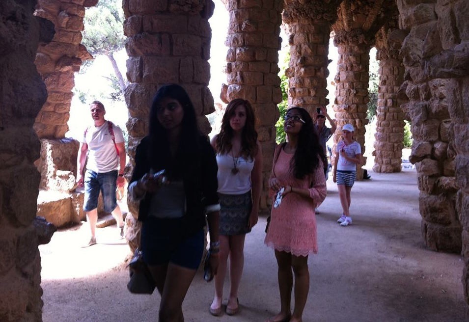 francesca sophia, blogger, stands with friends under an archway in barcelona