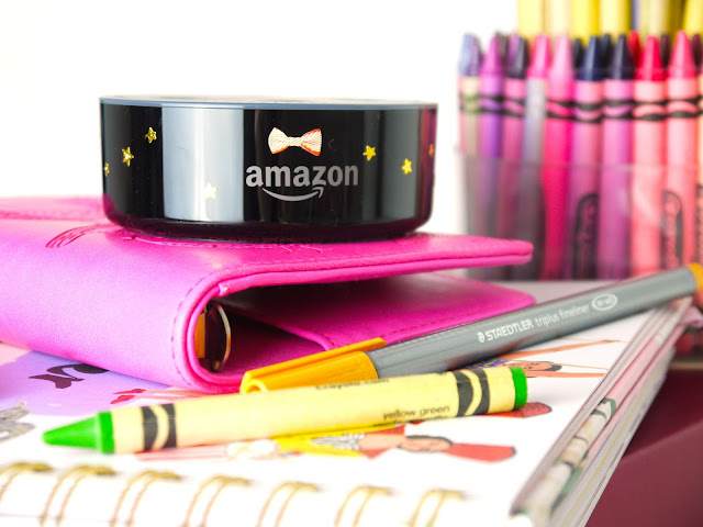 a black amazon echo dot sat on a pink book with bright crayons scattered around it