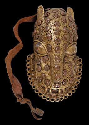 Photo of a leopard brass mask - the spots of the leopard are raised from the surface