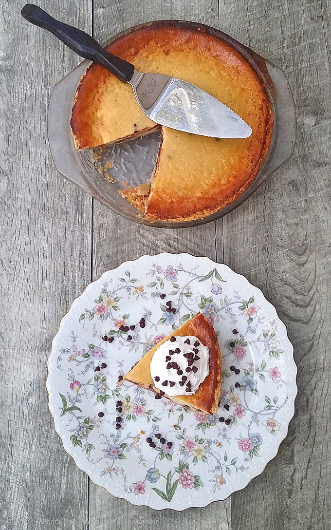 this is a photo of the best cannoli pie baked in the oven in a glass deep dish pie plate. It is on a wooden grey board and there is also a slice of pie on a pretty floral plate.