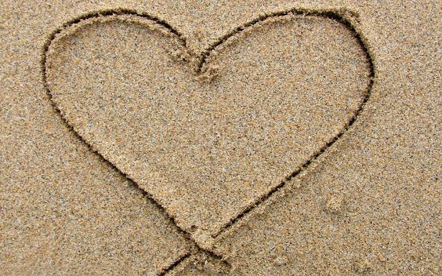 Foto met een hartje van zand op het strand