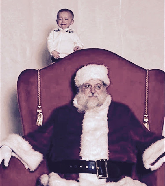 Photo with Santa. Screaming kid behind Santa's chair, while Santa looks exasperated. A Pleasant Christmas Story and other stories of Christmas Creepers. marchmatron.com