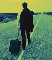 Ceketini omzuna atıp valiziyle yolun ortasında yürüyen bir adam