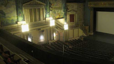 Large theater with painted murals on the far wall and a replica of a Greek temple with columns